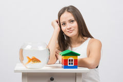 The girl sits at a table on which there is an aquarium with goldfish and toy house Stock Photos