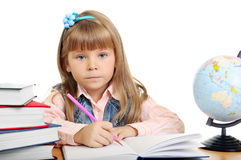 Girl sits at a table and writes to writing-books Stock Photos