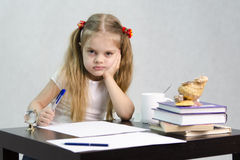 The girl writes on a piece of paper sitting at the table in the image of the writer Royalty Free Stock Images