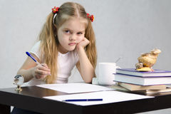 The girl writes on a piece of paper sitting at the table in the image of the writer Royalty Free Stock Image