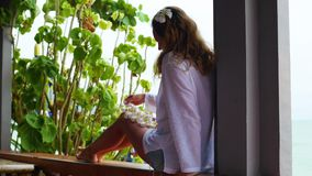 The girl sits on the terrace and looks towards the sea.Holding flowers in his hands. stock video footage