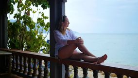 The girl sits on the terrace and looks towards the sea stock video footage