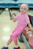 Girl sits and thumbs up in bowling club Stock Photos