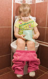 Girl sits on a toilet bowl Royalty Free Stock Image