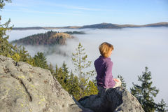 Girl sits on top of a mountain, looking at around royalty free stock photos