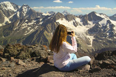 Girl sits on the top of the mountain and take pictures Stock Image