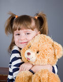 Girl sits  with a toy bear Royalty Free Stock Photo