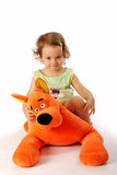 A girl sits on a toy dog. Stock Image