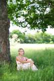 A girl sits in a tree. Beautiful girl in a long bright dress sitting in the grass near a tree trunk Stock Images