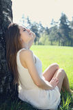 Girl sits under the tree Stock Photos