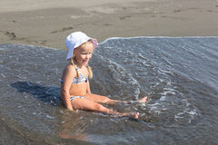 Girl sits at the water's edge Stock Photography