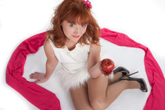 The girl sits on a white background with an apple. This image has attached release Stock Photo