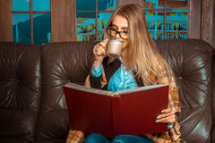 A girl sits at a window on the couch, reading a book and drinkin stock photo