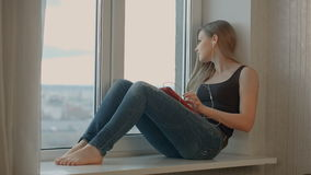 Girl sits on window listen music and works with stock video footage