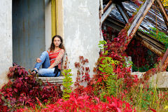 Girl sits in the window opening. Of the old ruined building next to the metal beams Royalty Free Stock Photography