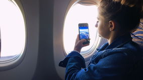 The girl sits at the window of the plane and takes a picture from the window. stock video