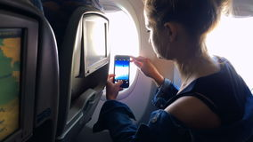 The girl sits at the window of the plane and takes a picture from the window. stock video footage