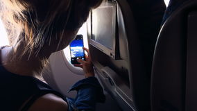The girl sits at the window of the plane and takes a picture from the window. stock footage