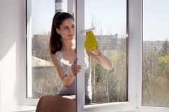 Girl sits on a window sill and washes a window