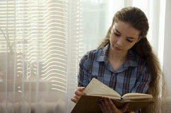 Girl sits by the window and thumbs a notepad Stock Images