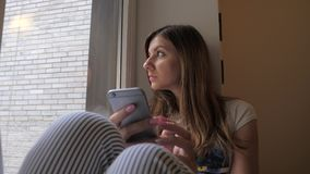 The girl sits on the windowsill, looks out the window, uses the phone. stock video footage