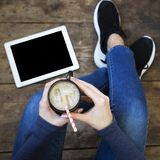 The girl sits on a wooden floor and holds ice latte in her hands. Tablet on the floor. Top view stock photo