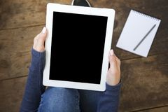 The girl sits on a wooden floor and holds a tablet with a blank stock photos