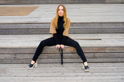 The girl sits on a wooden platform Stock Photography