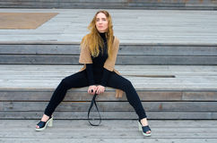 The girl sits on a wooden platform Stock Photos