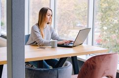 The girl sits working at the computer stock image