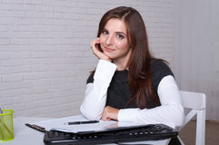 Girl sits at a workstation propped her head on her hand Royalty Free Stock Photo