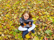 Girl sits on the yellow leaves in the park Royalty Free Stock Photos