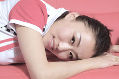 Girl sitting. Lying on the couch in the dark red hair Chinese girl Stock Photo