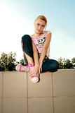 Girl sitting. Girl with hands on her feet looking at camera Royalty Free Stock Photo