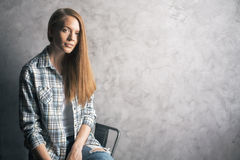 Girl sitting against blank wall Stock Images
