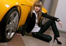 Girl sitting against of yellow car Royalty Free Stock Photos