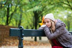Girl sitting alone on the bench on a fall day Royalty Free Stock Image