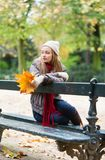 Girl sitting alone on the bench on a fall day Stock Image