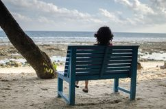 Girl Sitting Alone on a Bench near Seashore. Waiting for someone royalty free stock photos