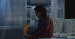 Girl sitting alone in her bedroom stock image