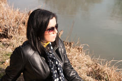 Girl and river. Girl sitting alone on the river bank and sad Royalty Free Stock Photography