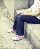 Girl sitting alone in the schoolyard Royalty Free Stock Images