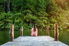Girl sitting alone on a the wooden bridge on the lake. Pang Ung, Thailand stock photos
