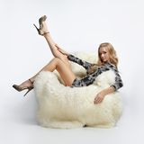 Girl sitting in arm-chair. Portrait of beautiful blonde blue-eyed girl sitting in big furry arm-chair Royalty Free Stock Images