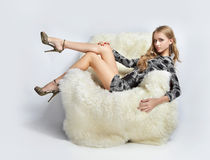Girl sitting in arm-chair. Portrait of beautiful blonde blue-eyed girl sitting in big furry arm-chair Royalty Free Stock Photo