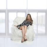 Girl sitting in arm-chair. Portrait of beautiful blonde blue-eyed girl sitting in big furry arm-chair Stock Photo