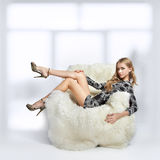 Girl sitting in arm-chair. Portrait of beautiful blonde blue-eyed girl sitting in big furry arm-chair Royalty Free Stock Photos