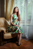 Girl sitting on a an armchair. Royalty Free Stock Photos
