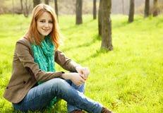Girl Sitting At Green Grass At Park. Stock Photo