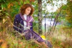 Girl sitting on autumn grass Royalty Free Stock Photo